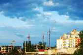 Residential building site with cranes and stormy clouds — Stock Photo