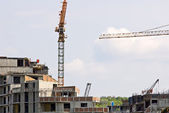 Residential building site with tower crane and blue sky — Stock fotografie