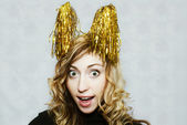 Girl with party golden tinsel horns — Stock Photo
