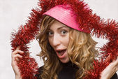 Girl with pink hat and red tinsel — Stock Photo