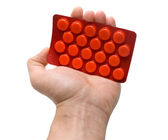 Hand holding package with red tablets — Stock Photo