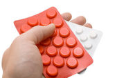 Hand holding a red and white pills — Stock Photo