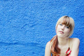 Blonde against blue plaster wall — Stock Photo