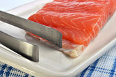 Salmon fillet and a tongs — Stock Photo