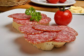 Slice poppy seed bread with salami — Stock Photo