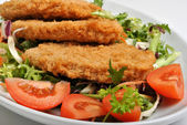 Breaded fish steak with organic herbs — Stock Photo