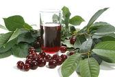 Cherry juice and red cherries — Stock Photo