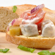 Herring salad on bread - Stock Photo