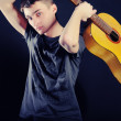 Young fellow with a guitar on a black ba — Stock Photo