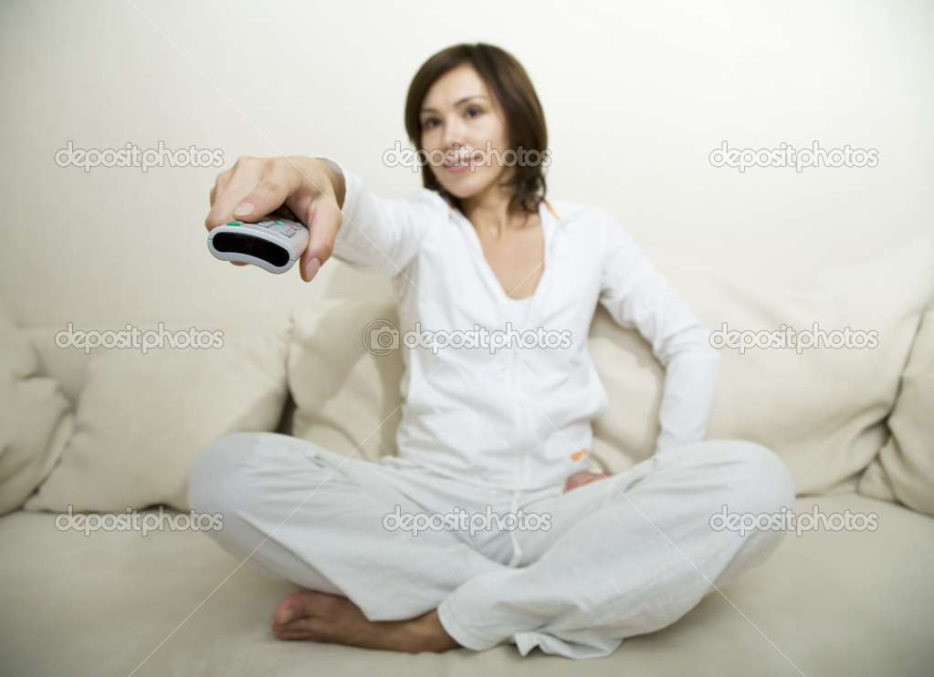 Young woman hold remote control in her hand — Stock Photo #1599391