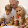 Grandpa is teaching his grandchildren to draw — Stock Photo #1725212