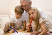 Grandpa is teaching his grandchildren to draw — Stock Photo