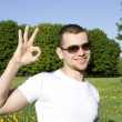 Stock Photo: Guy in park. Sign ОК