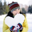 Girl bitten snowy heart — Stock Photo
