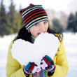 Girl bitten snowy heart — Stock Photo #1812344