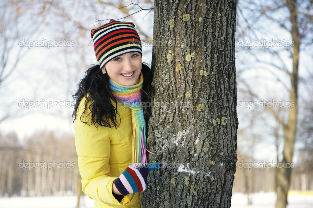Girl in a yellow jacket in the park in winter snowball, hiding behind a tree — Stock Photo #1812844