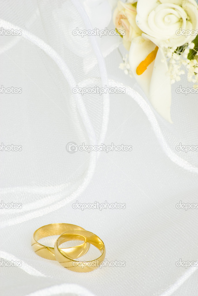 Wedding rings and flowers decorations over bridal veil — Stock Photo #1554019