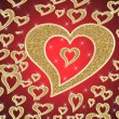 Golden hearts on red background — 图库照片