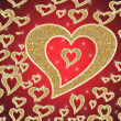 Golden hearts on red background — Stock Photo
