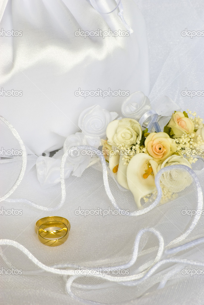 Bridal bag and wedding rings flowers decorations over bridal veil
