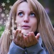 Girl blowing snowflakes - Stock Photo