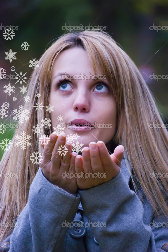 Pretty girl blowing white snowflakes to the camera — Stock Photo #2070215