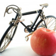 Toy bike next to red apple — Stock Photo #2544270