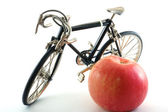 Toy bike next to red apple — Stock Photo