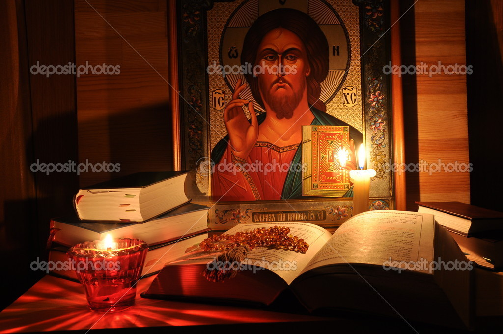 Russian Icon Pantocrator, the Almighty, books and candle's flame. — Stock Photo #1711706