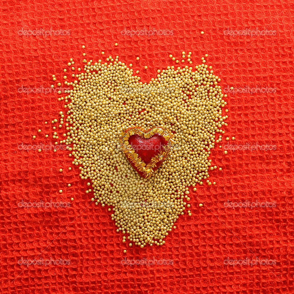 Heart and bisser on red textile background — Stock Photo #1733635
