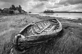 Old fishing unpainted wooden boat ashore — Stock Photo