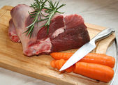 A joint of lamb ready for cooking,with carrots and rosemary — Stock Photo