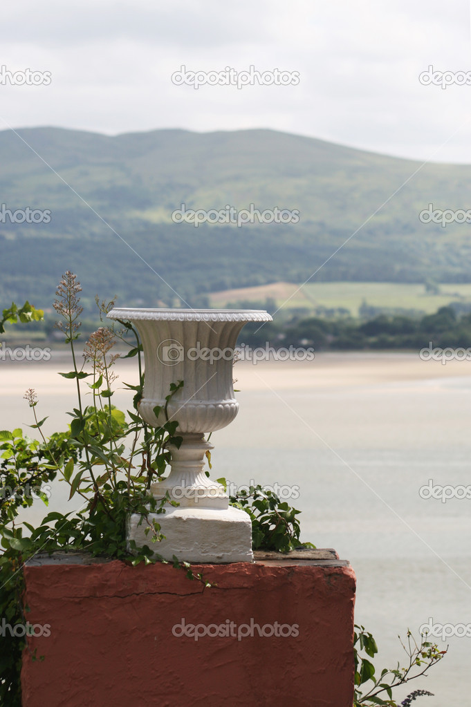 An elegant white urn stands on a plinth, entwines with plants. In the background is, just visible, a beautiful seascape — Stock Photo #1735392