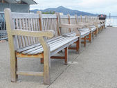 Row of wooden benches on the wharf — Stock Photo