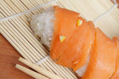 Salmon sushi on bamboo mat — Stock Photo