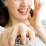 en leende flicka med en fjärrkontroll — Stockfoto #1699445