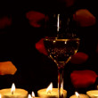 Wine glass and candles with petals — Stock Photo
