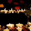 Stock Photo: Wine glass and candles with petals