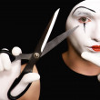 Stock Photo: Mime with scissors on black background