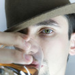 Royalty-Free Stock Photo: Young man in  hat with  glass of whisky