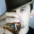 Young man in hat with glass of whisky — Stock Photo #1587938