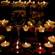 Stock Photo: Wine glass and candles with petals roses