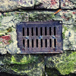 Water drain lattice on brick surface — ストック写真