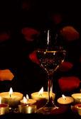 Glas wijn en kaarsen met bloemblaadjes — Stockfoto