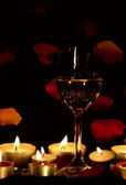 Wine glass and candles with petals — Foto de Stock