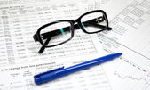 Glasses, pen and financial — Stock Photo