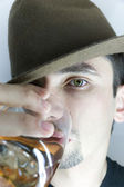 Young man in hat with glass of whisky — Stock Photo
