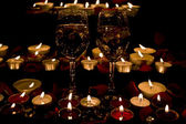 Wine glass and candles with petals roses — Photo