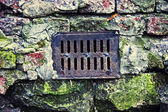 Water drain lattice on brick surface — Stock Photo