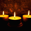 Three candles against a dark background — Stock Photo